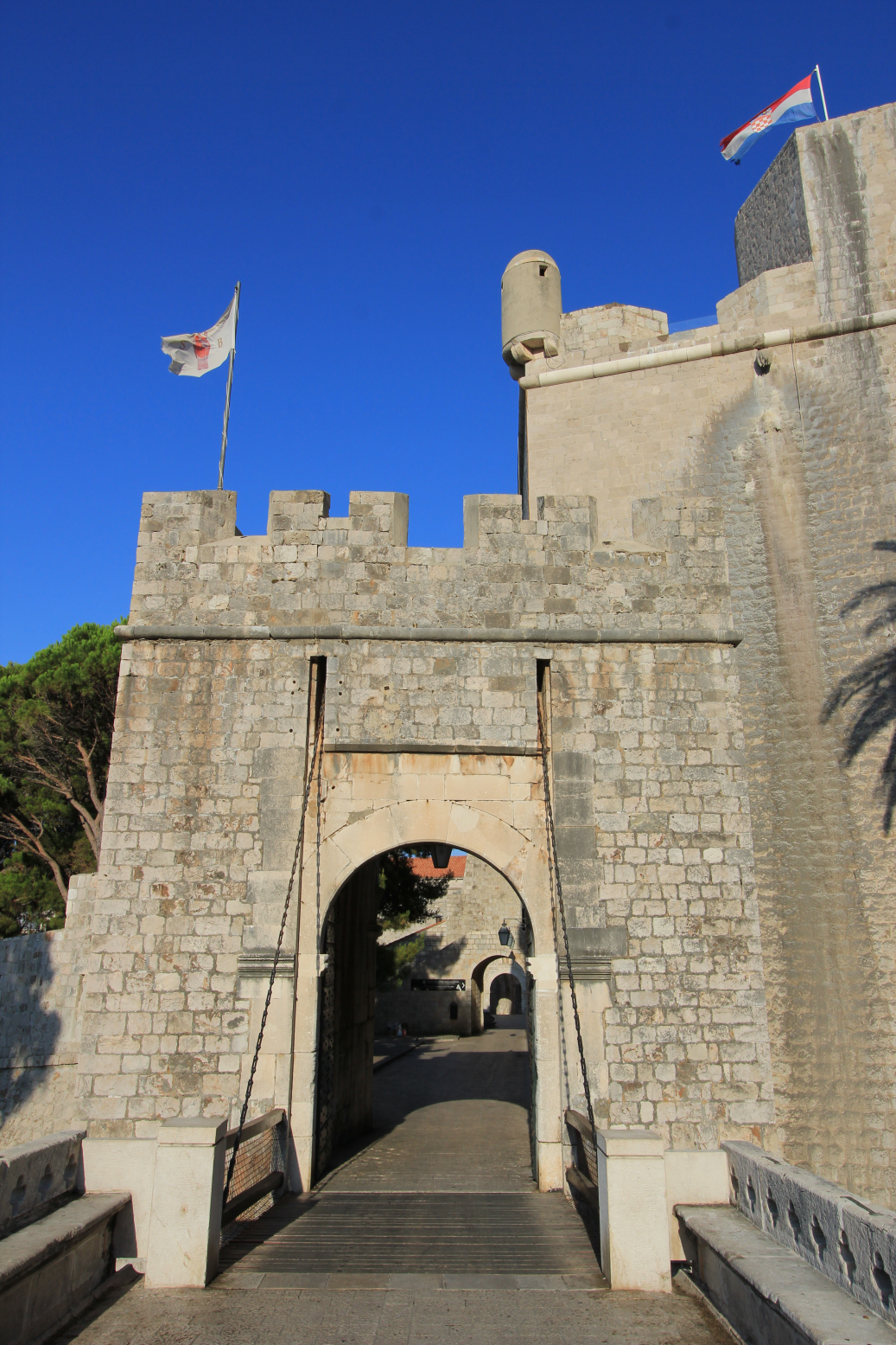 The national flag of Croatia and the Libertas flag of Dubrovnik fly in the morning sun at Ploče Gate