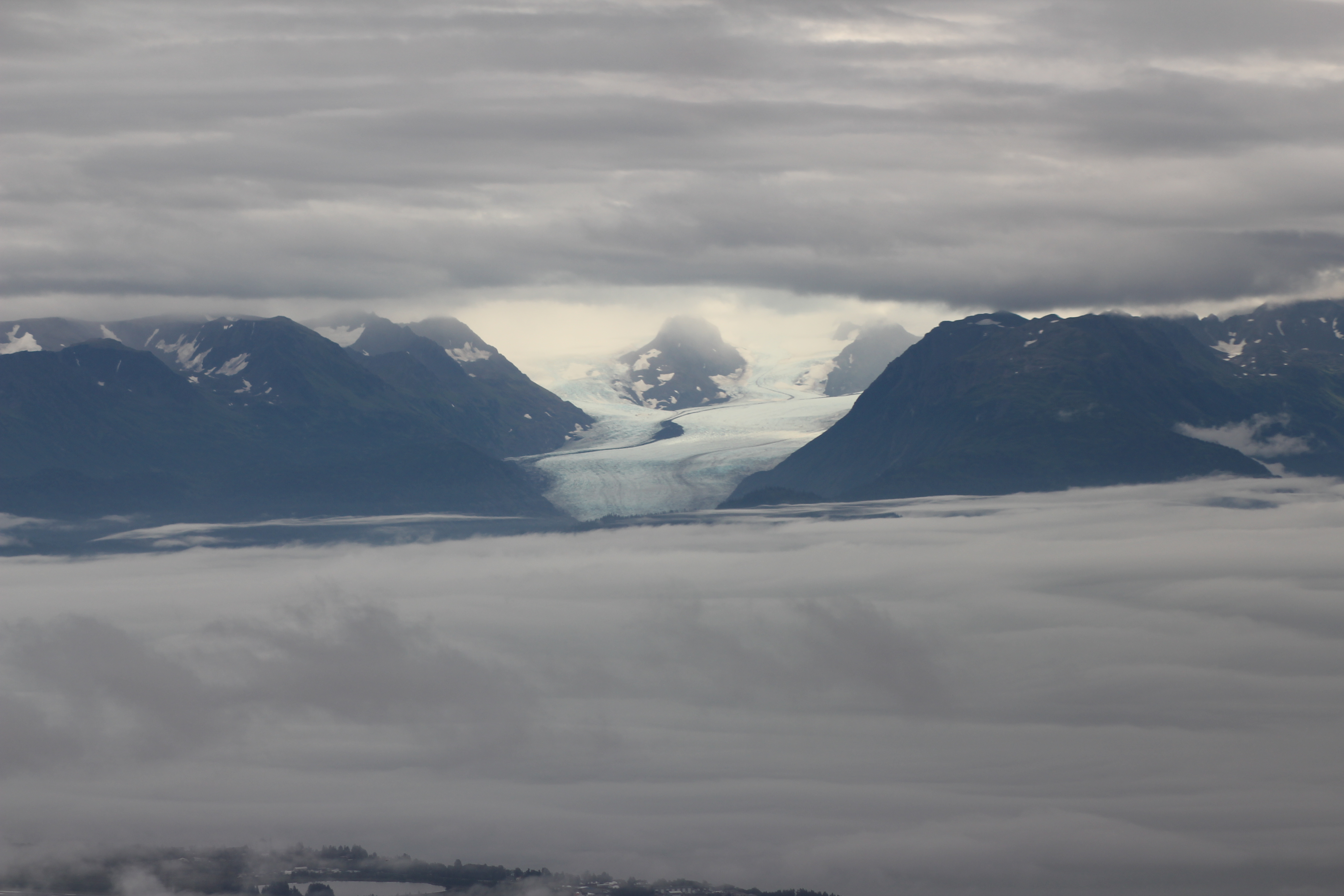 A slightly eerie view across the fog-covered Kachemak Bay to Grewingk Glacier with the coast between Fritz Creek and Kachemak/Miller's Landing just visible along the bottom of the image to the left.