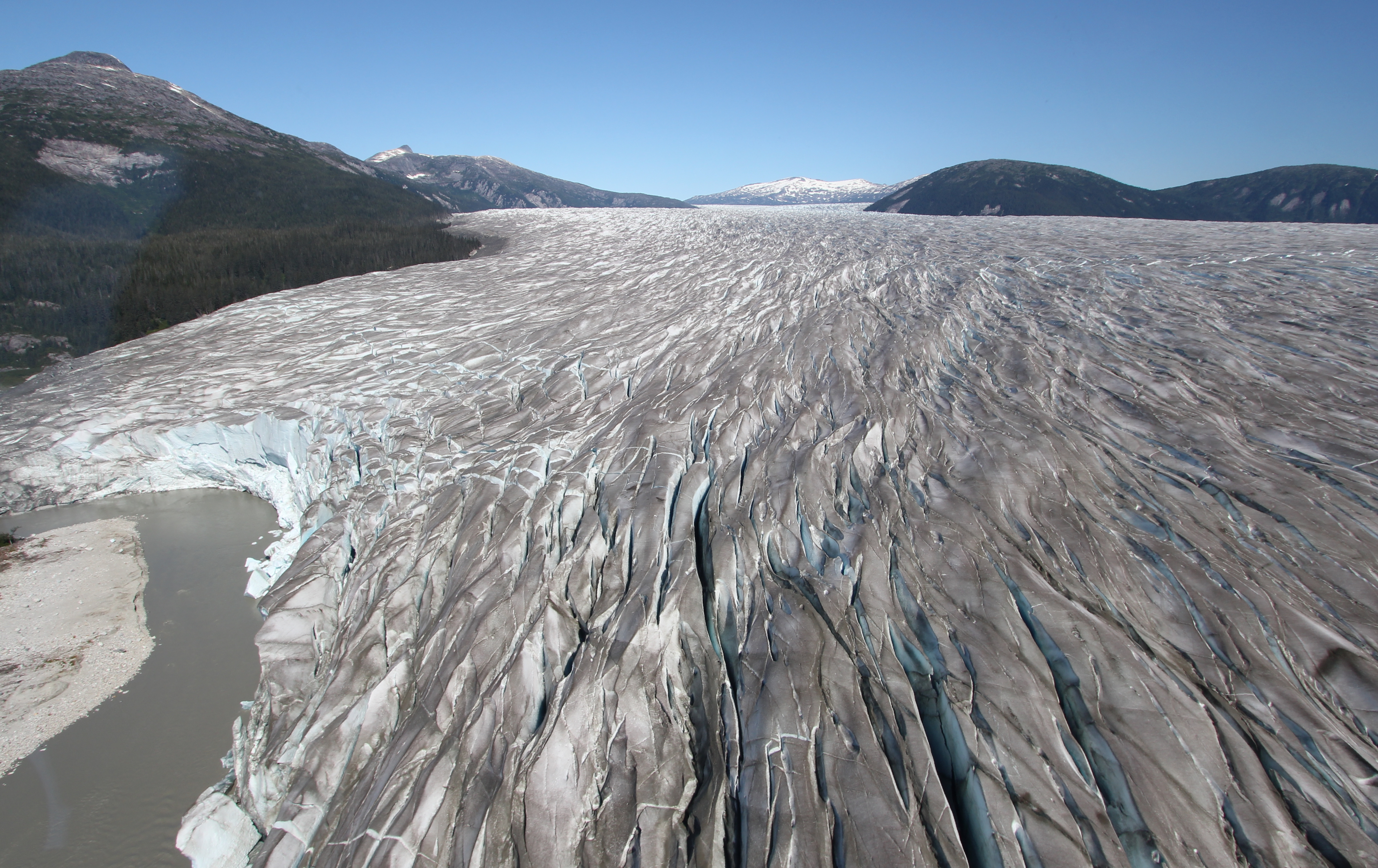 The view up Taku Glacier from the terminus. To the left is Norris Mountain (4,125 ft/1,257m), and to the right the Brassiere Hills. Click on the image to enlarge it and get a better idea of just how striking the crevasses are from above.