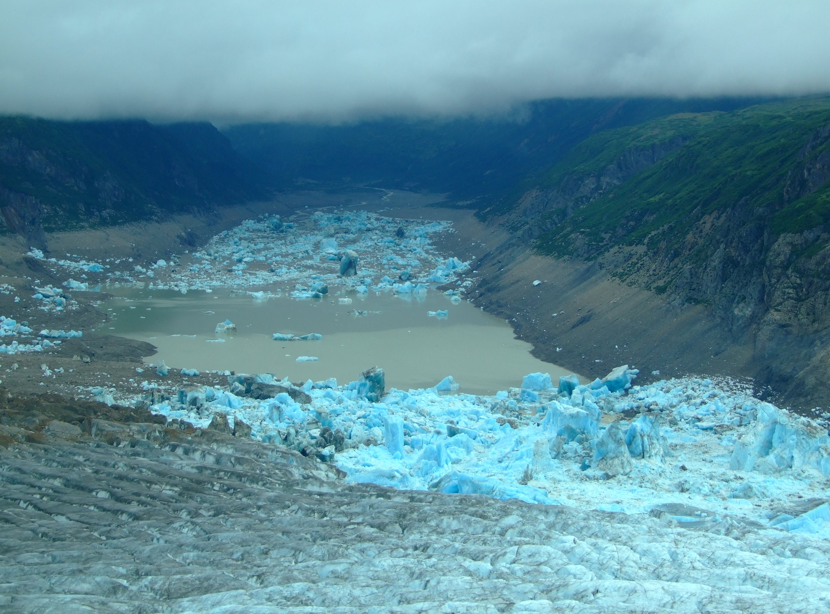 Under the impinging cloud layer, Strandline Lake was no longer impounded by the Triumvirate Glacier. Note the stranded glacial ice high on the sides of the lake's edges. This view of its remaining waters, and the previous images of its continued outflow, show that it wasn't yet finished draining.