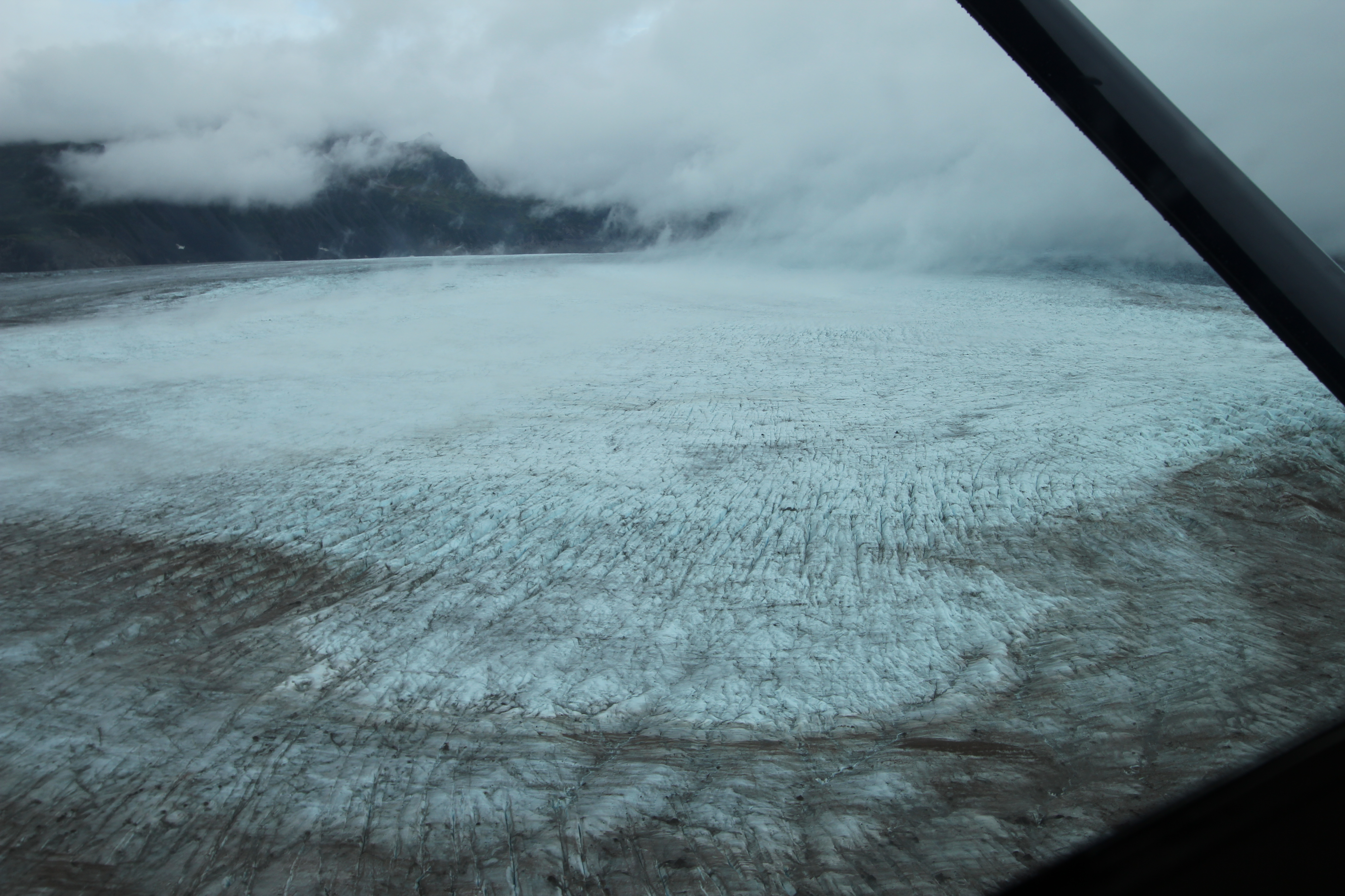 Flying up above the Triumvirate Glacier the weather was closing in, but our pilot, John Ellison, skilfully managed to get us through the turbulence between the clouds flowing down from the Tordrillo Mountains and the ice below to reveal the source of the flood…