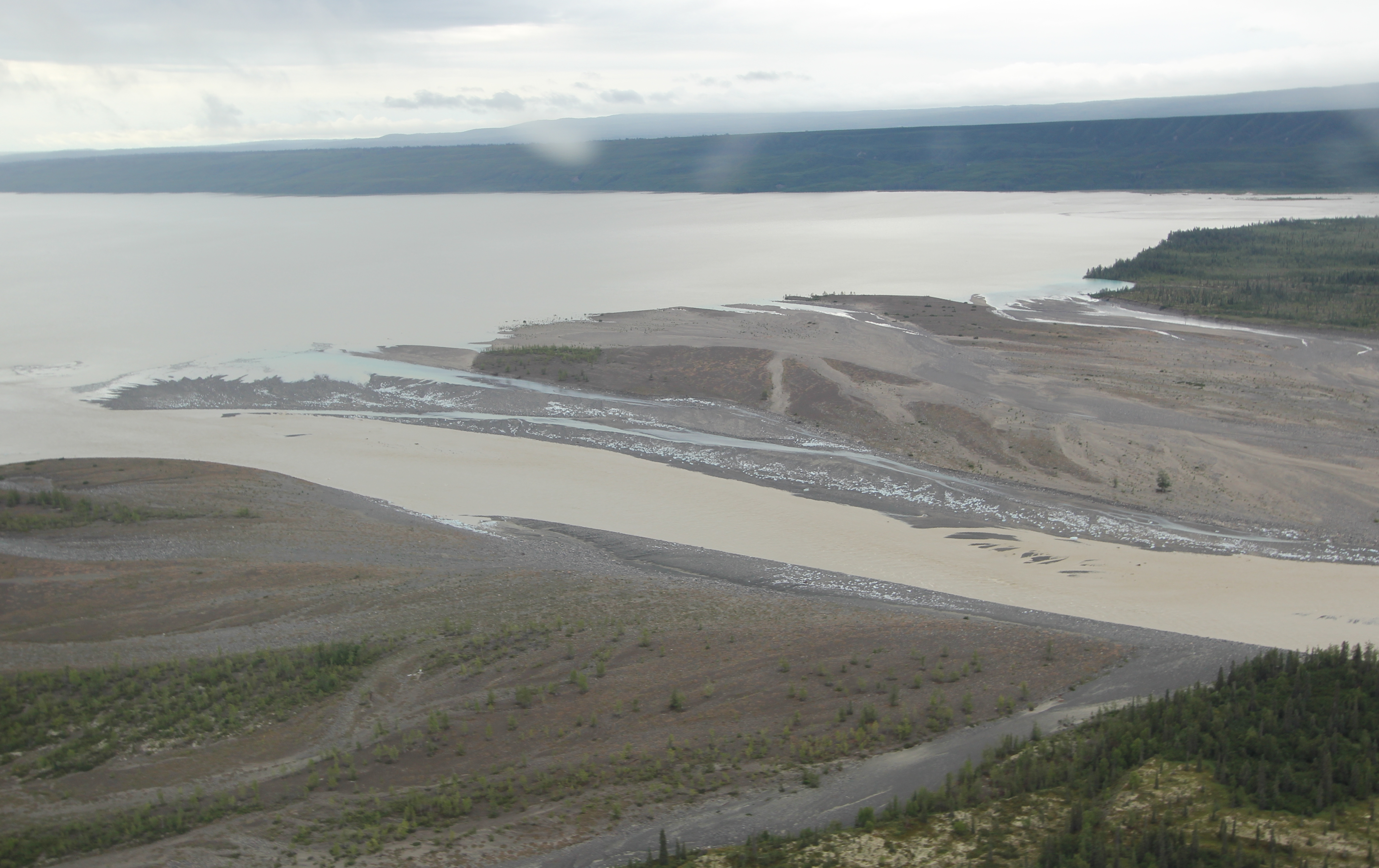 The trees at the periphery of the lake had been inundated by a rapid expansion of the water level and, closer to the, land in front of the Glacier, there were boulders of blue ice littering the banks of the principal northern riverine channel and braided streams flowing into the lake.